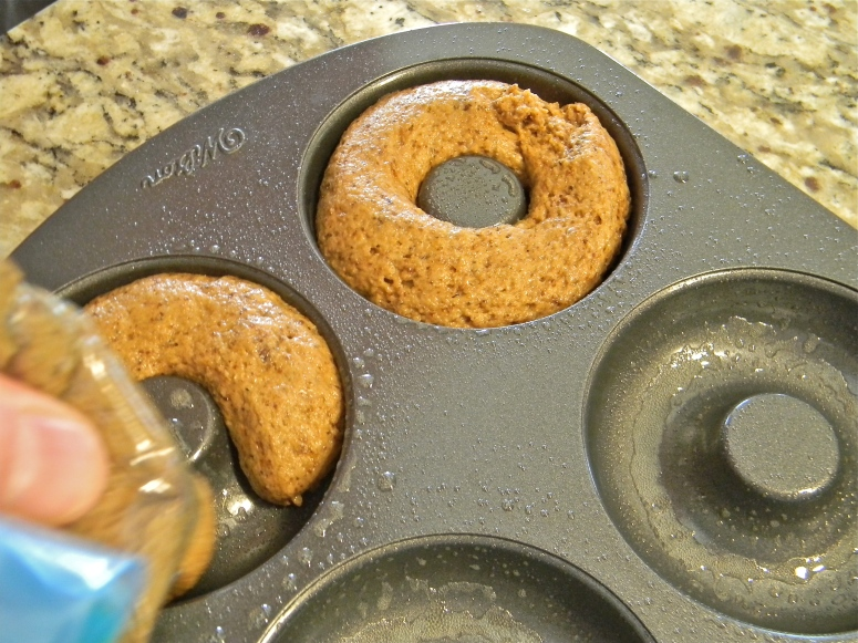 Scoop dough into a quart size baggie. Cut off one of the bottom corners, and squeeze into donut pan.